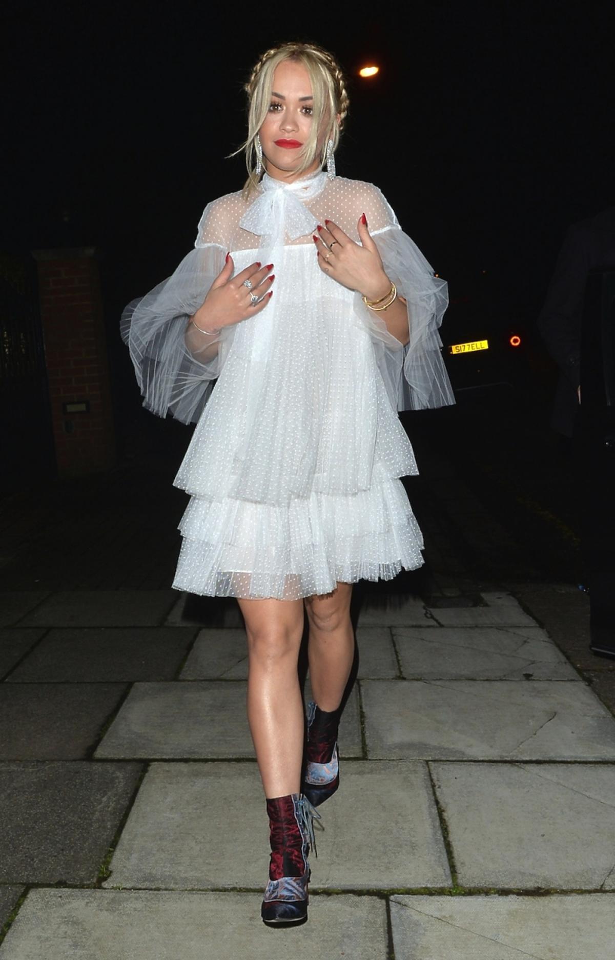 Rita Ora w białej tiulowej sukience z falbankami i z czerwoną szminką