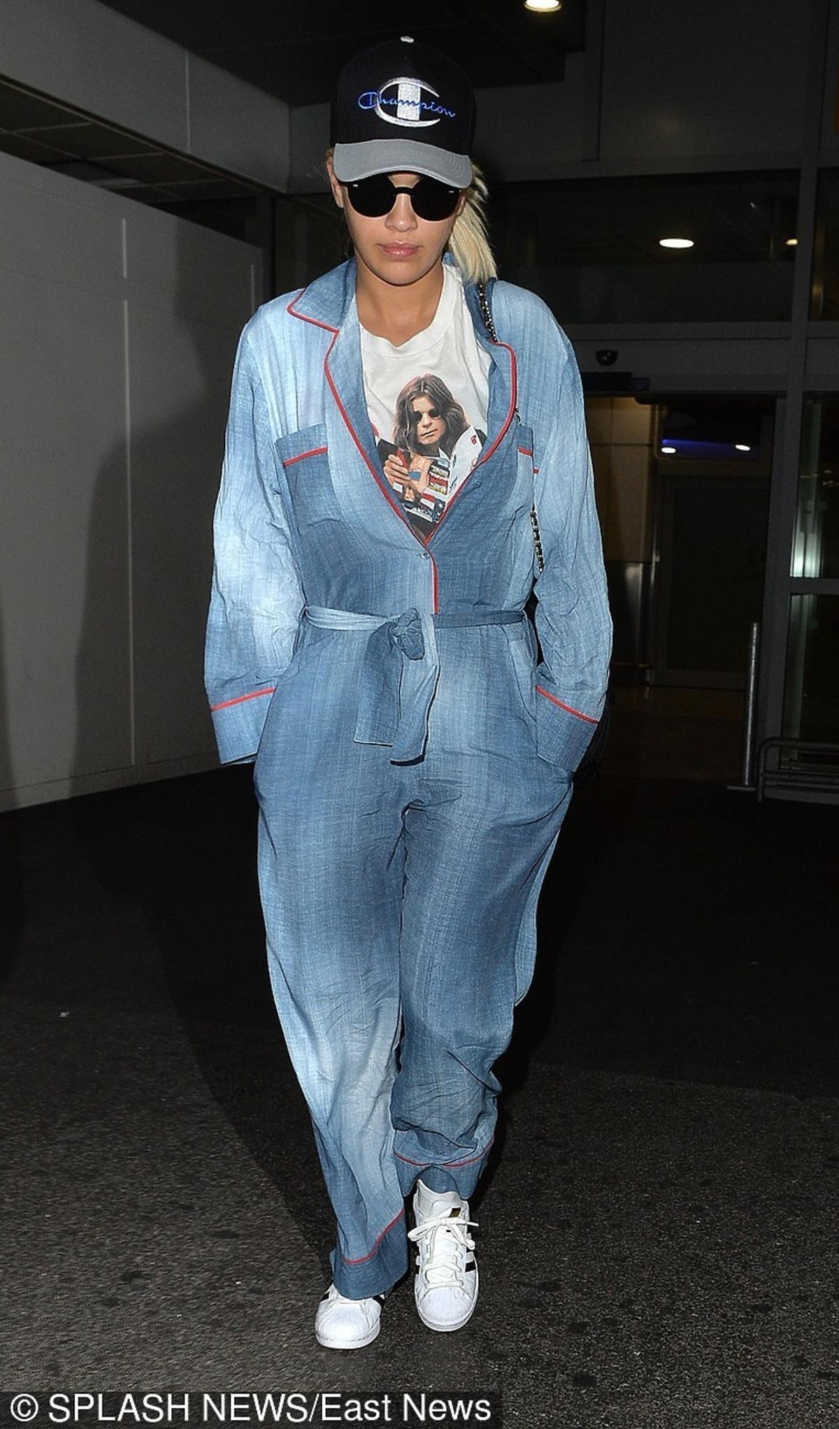 Rita Ora w dżinsowym kombinezonie, białek koszulce z nadrukiem  z czapekczką z daszkiem