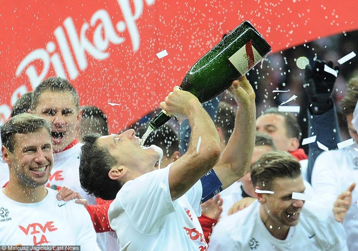Robert Lewandowski pije szampana po zakończonym zwycięstwem meczu piłki nożnej przeciwko Irlandii