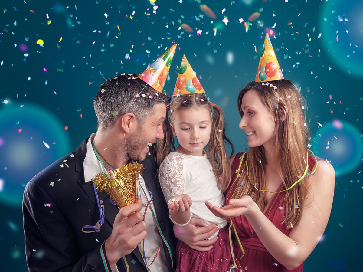 rodzice z córką w ozdobnych-czapkach świętują Sylwestra