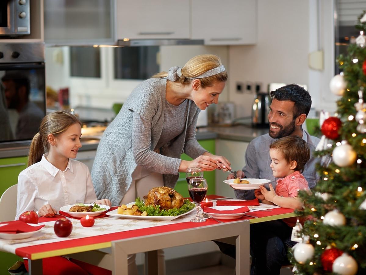 rodzina jedząca przy stole na tle choinki