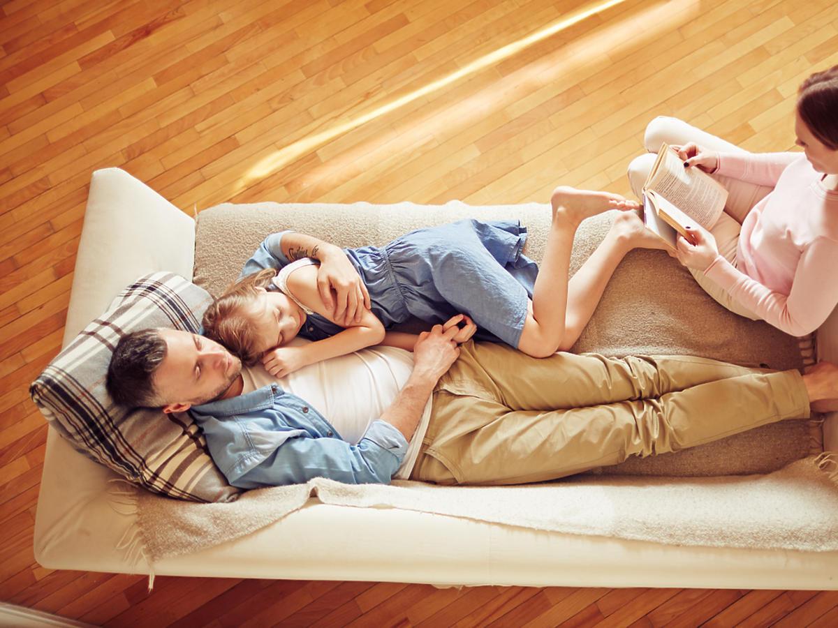Rodzina (matka, ojciec i dziecko) odpoczywa na kanapie.