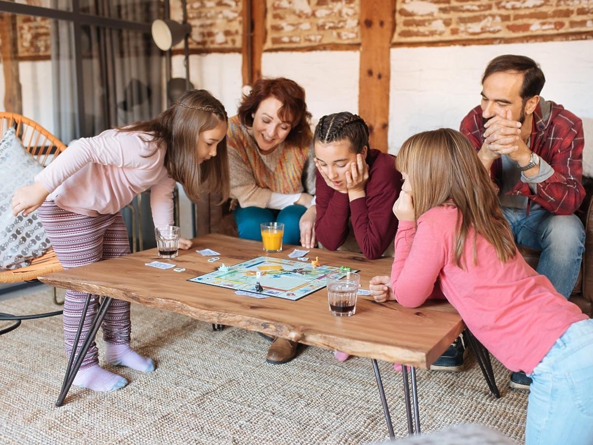Rodzina z dziećmi siedzi nad grą planszową.