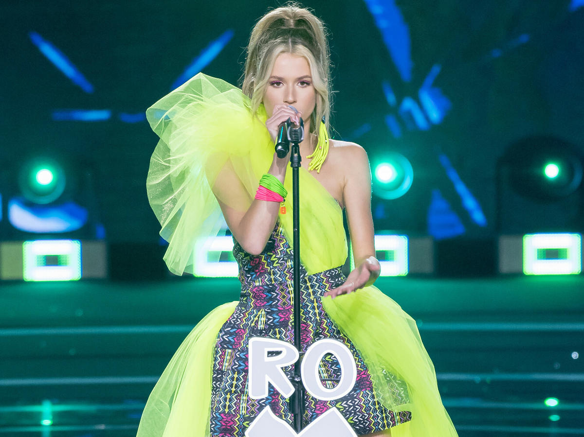Roksana Węgiel na scene sopockiej Opery Leśnej, w zielonej sukience, śpiewa do mikrofonu z napisem Roxie