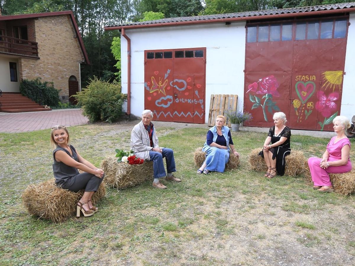 Eugeniusz, Krystyna, Stasia, Lilianna i Marta Manowska siedzą na stogach siana na podwórzu przed finezyjnie pomalowaną stodołą w programie Rolnik szuka żony