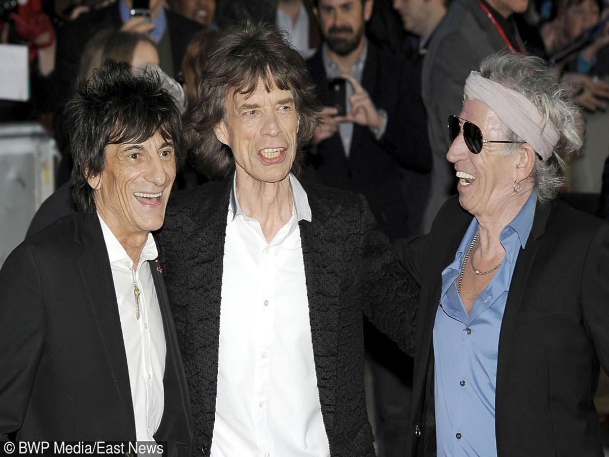 Ronnie Wood, Mick Jagger i Keith Richards w czarnych marynarkach obejmują się iśmieją