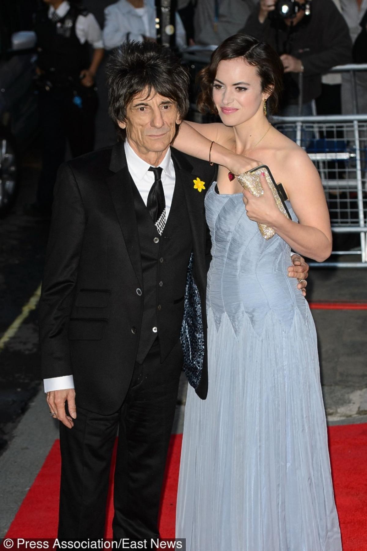 Ronnie Wood w czarnym garniturze i opierająca się o niego Sally Humphreys w niebieskiej sukni