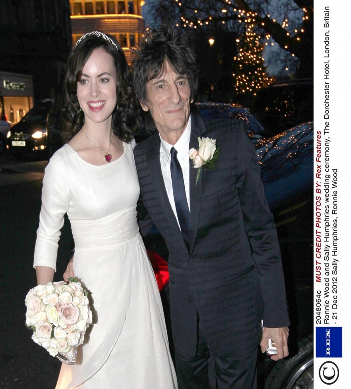 Ronnie Wood w czarnym garniturze i Sally Humphreys w suknie ślubnej obejmują się