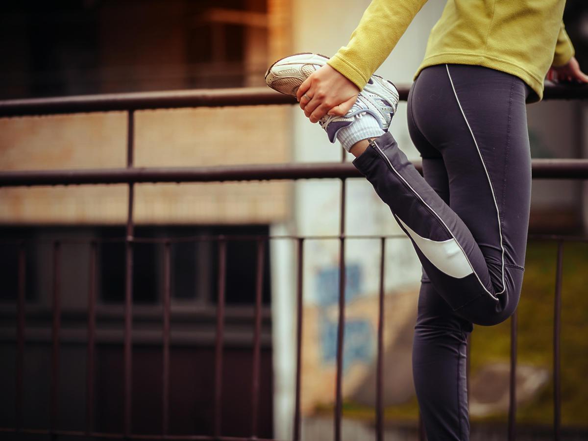 rozciąganie nóg przez biegacza
