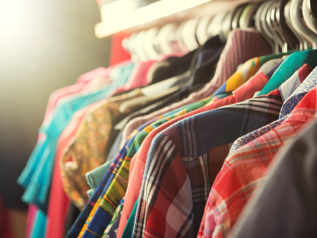Różnego rodzaju ubrania wiszą na wieszaku.