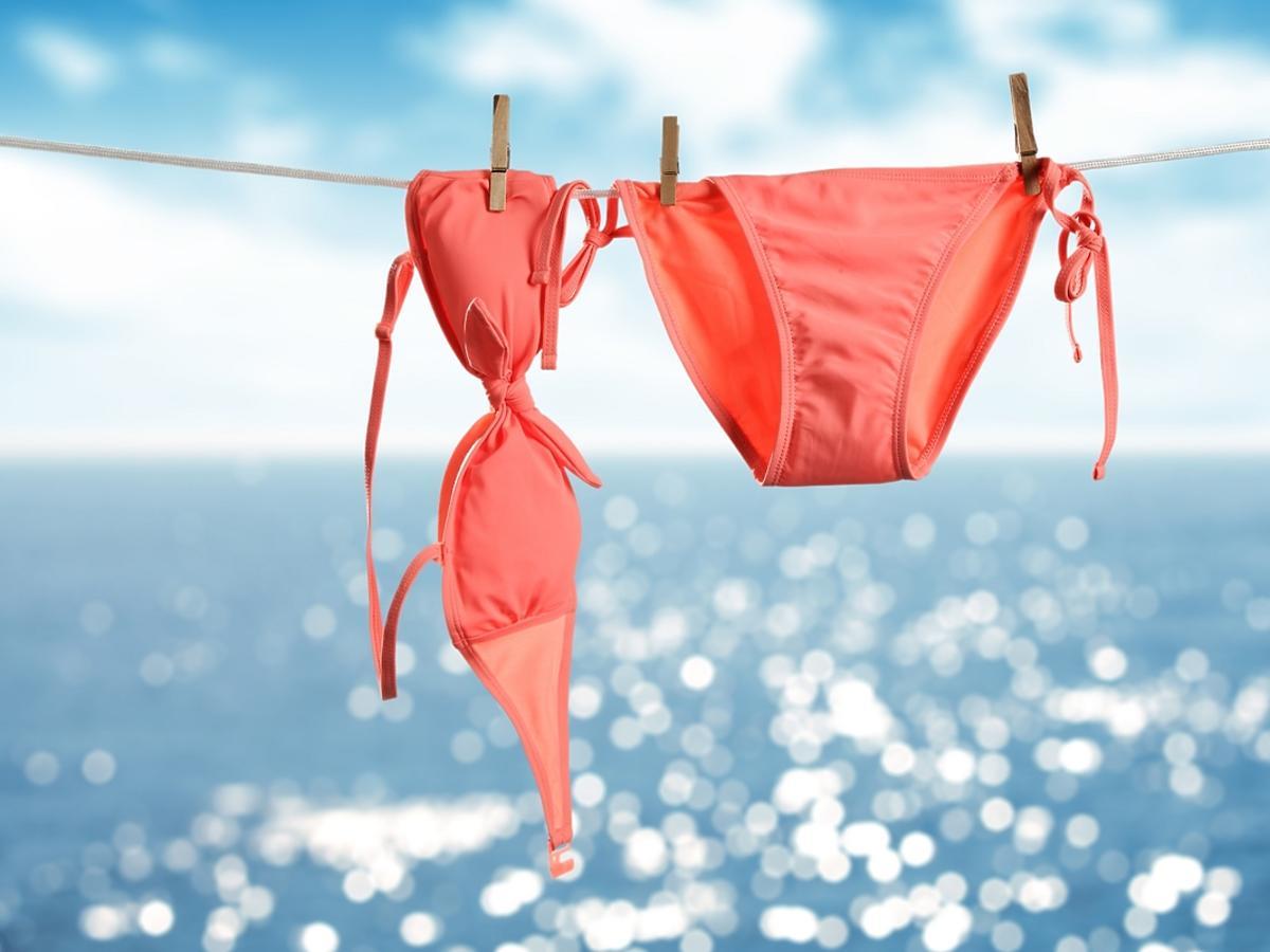 Różowy strój kąpielowy wisi na sznurku.