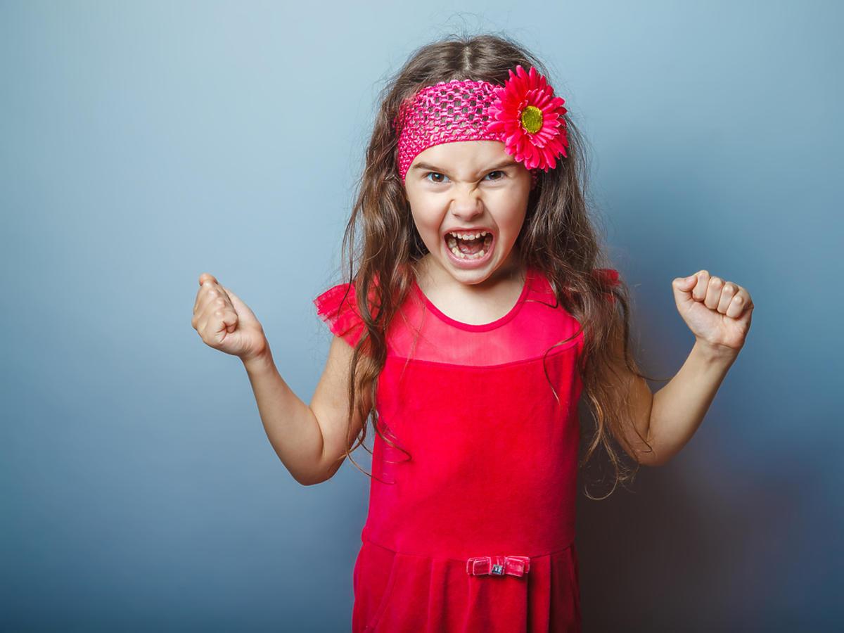 Rozzłoszczona dziewczynka krzyczy, ma ręce zaciśnięte w pięści