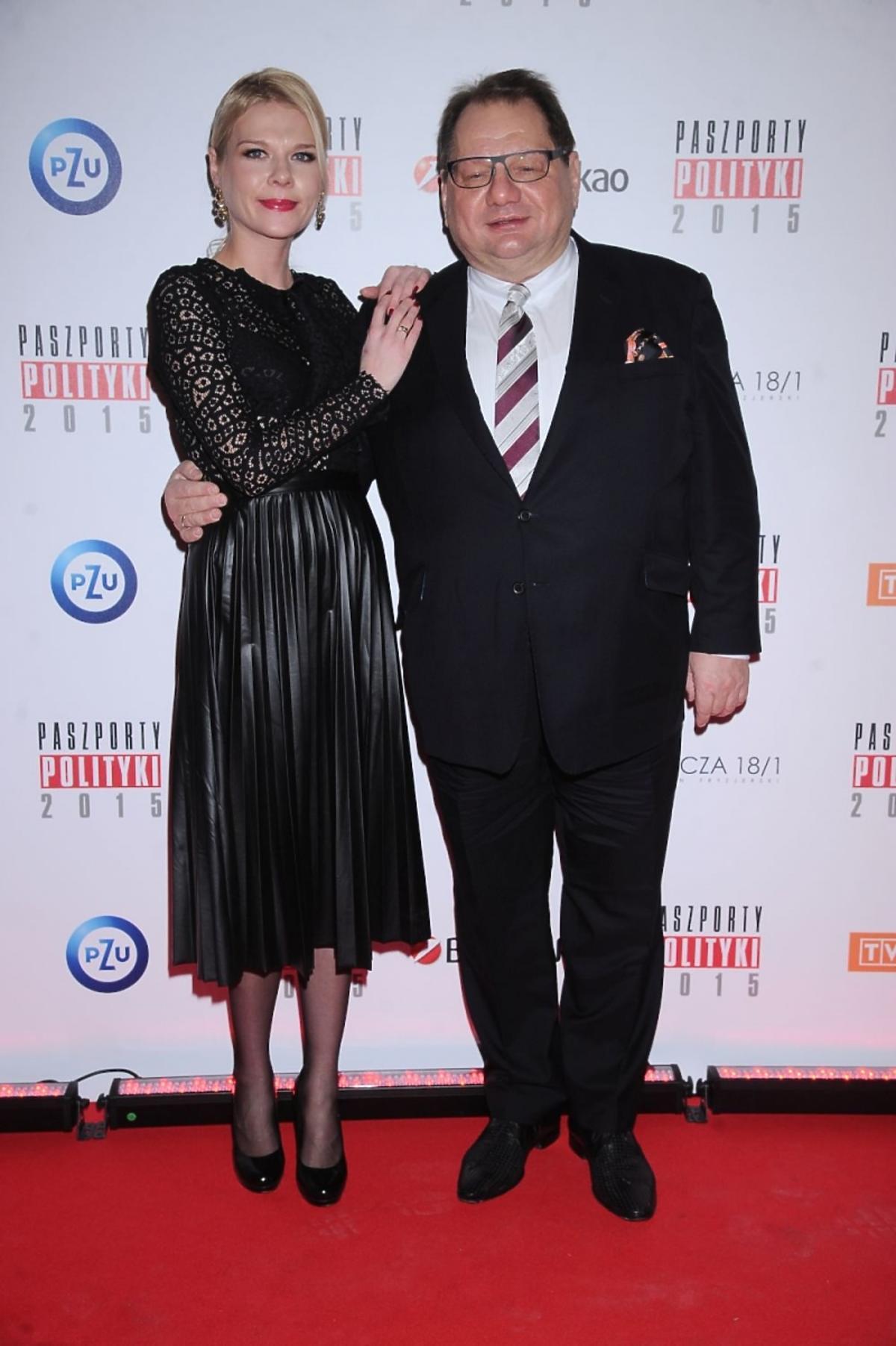Ryszard Kalisz w ciemnych garniturze z żoną Dominiką na ściance