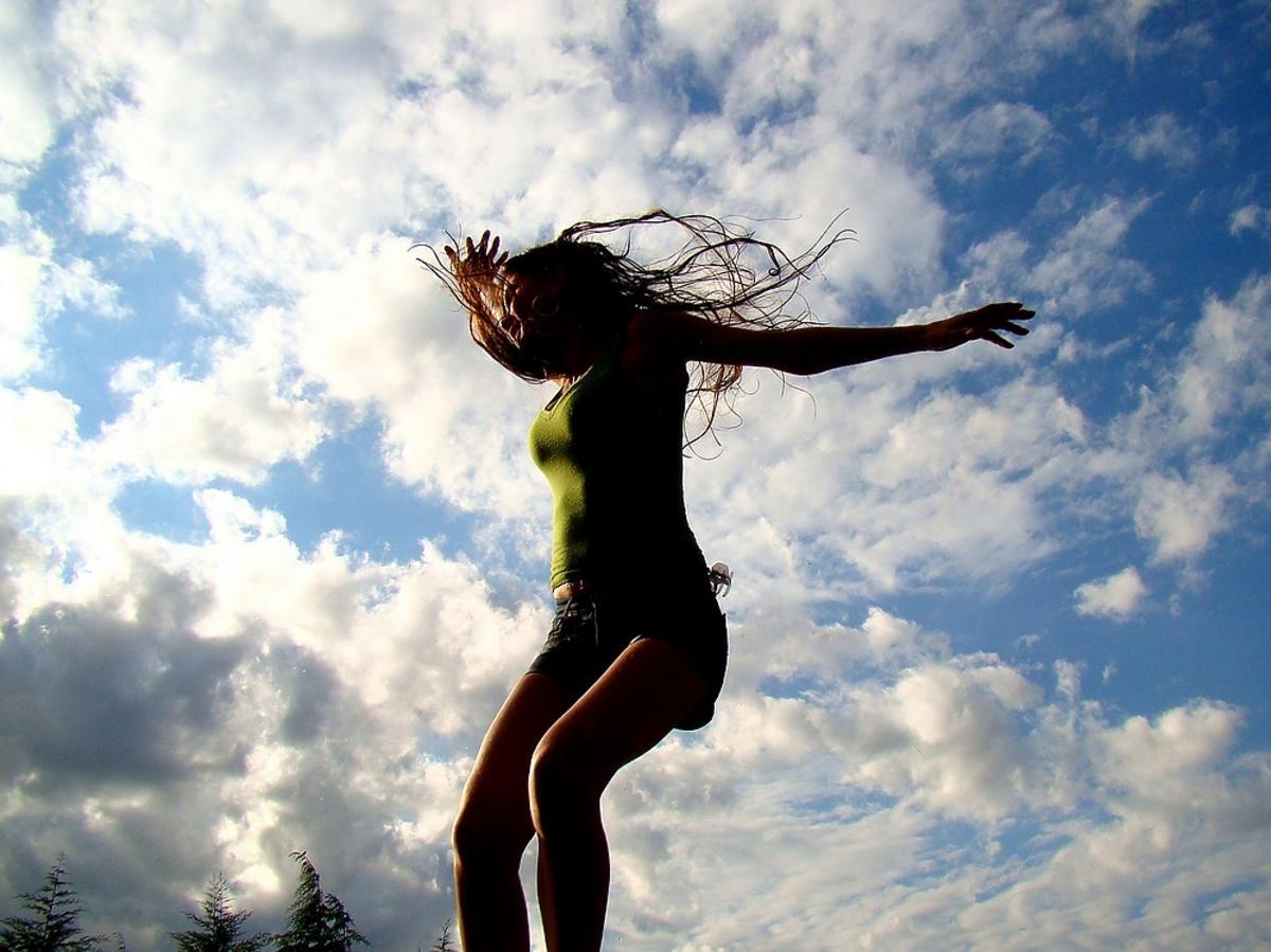 skacząca kobieta w tle chmur