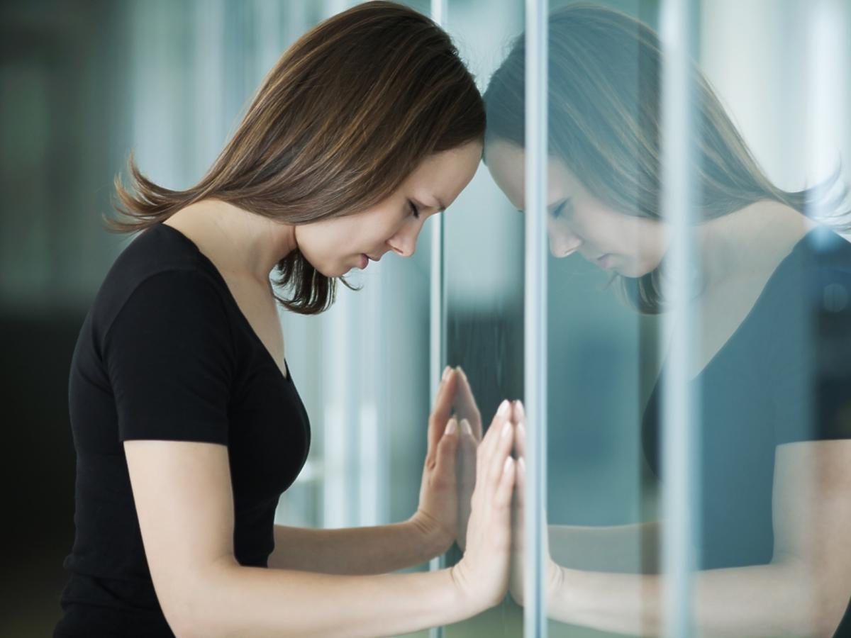 smutna dziewczyna opiera się o szybę w oknie