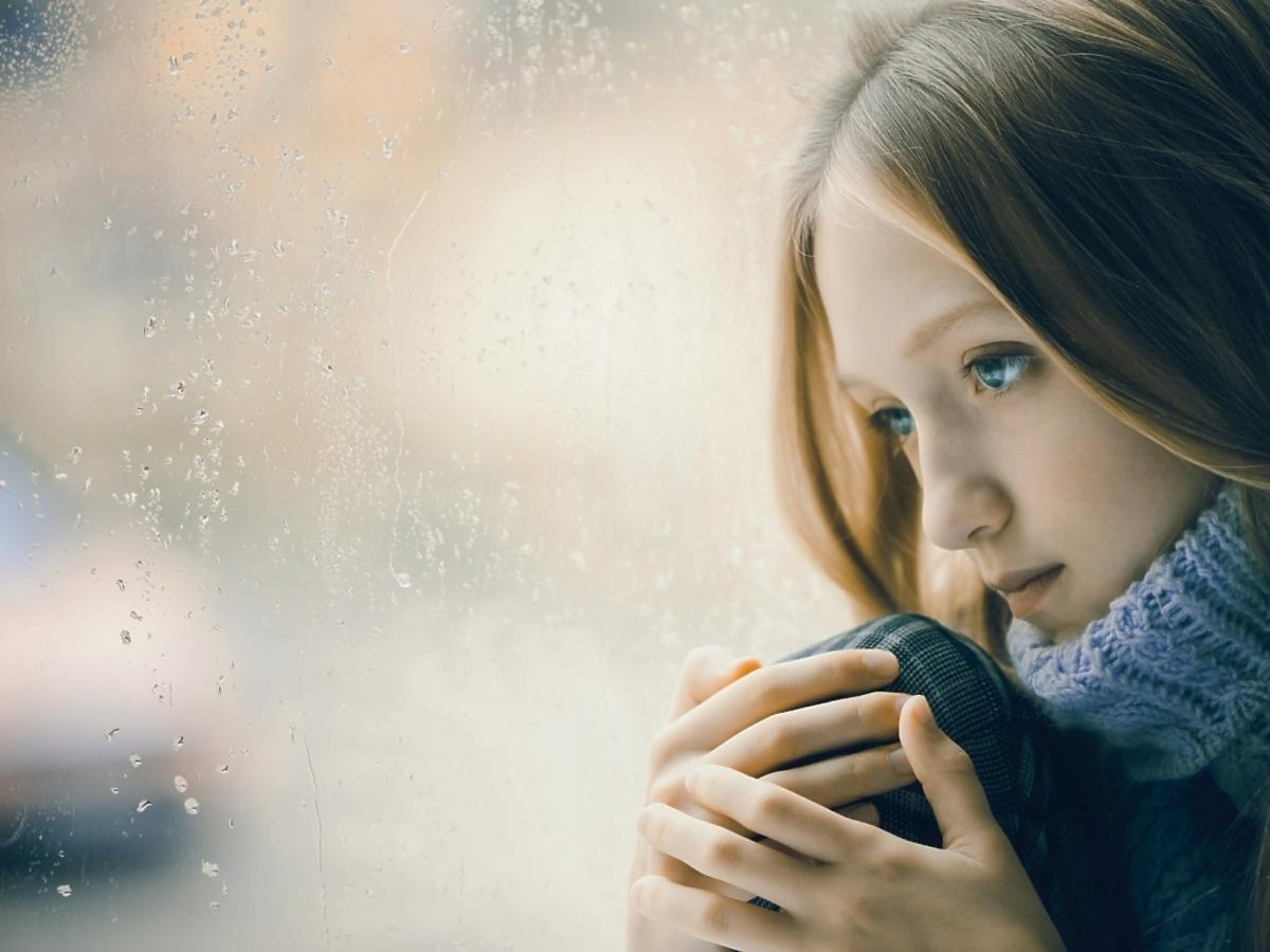 Smutna dziewczyna siedzi przy oknie