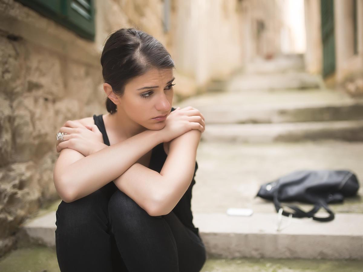 smutna kobieta siedząca na schodach