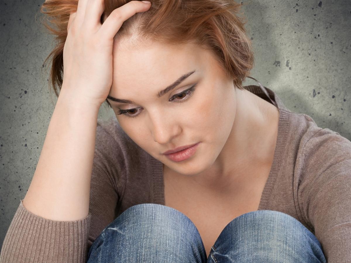 smutna kobieta trzyma się za głowę