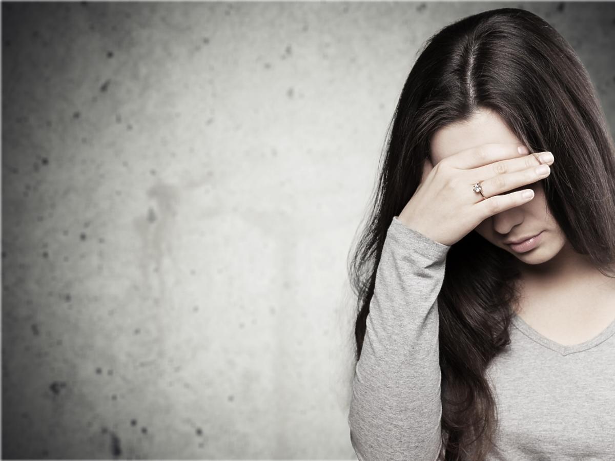Smutna kobieta zasłania sobie twarz ręką