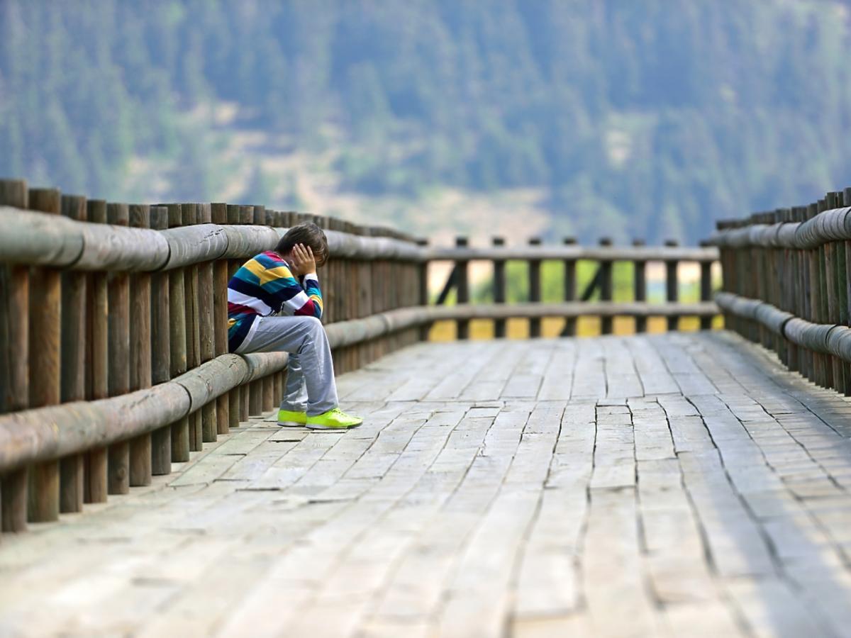 smutny chłopiec siedzi sam