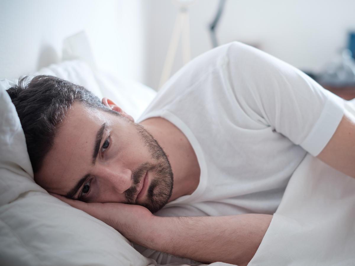 smutny mężczyzna leżący-w łóżku