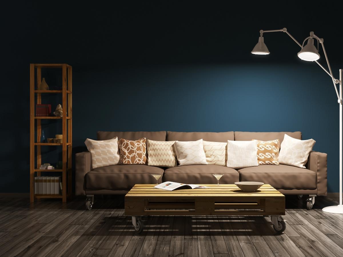 sofa z poduszkami i delikatne punktowe oświetlenie pokoju