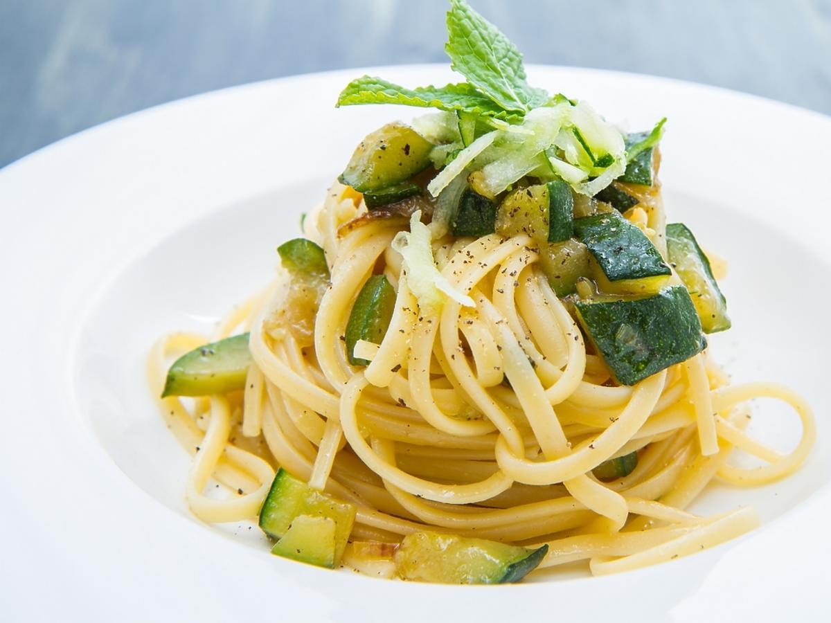 Spaghetti z pokojoną w kostkę cukinią na białym talerzu