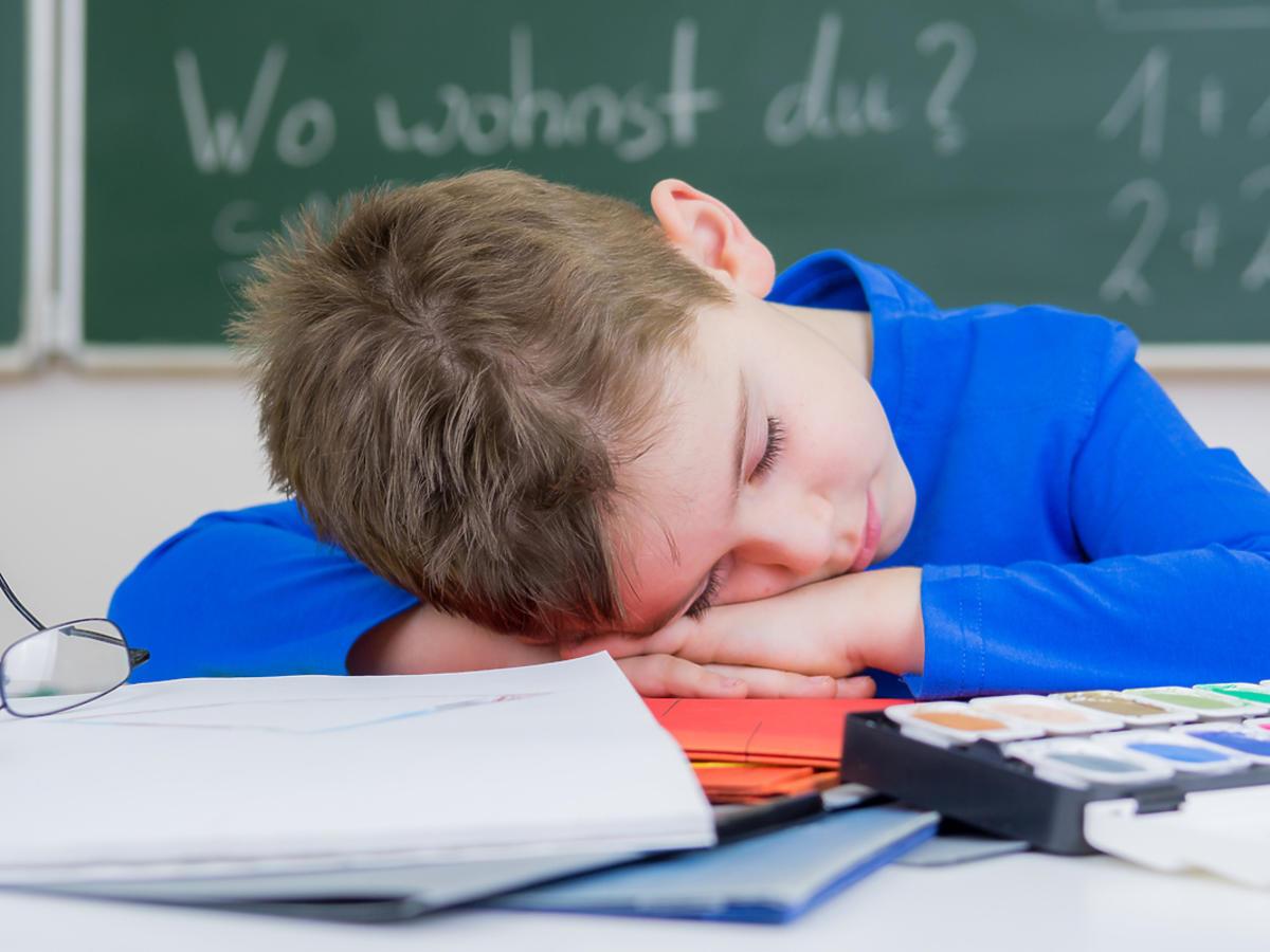 śpiący chłopiec w szkole