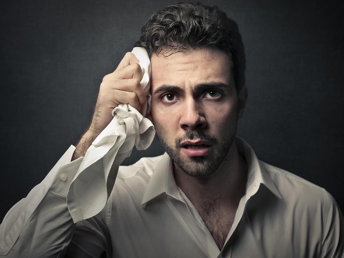 Spocony mężczyzna ociera pot z twarzy