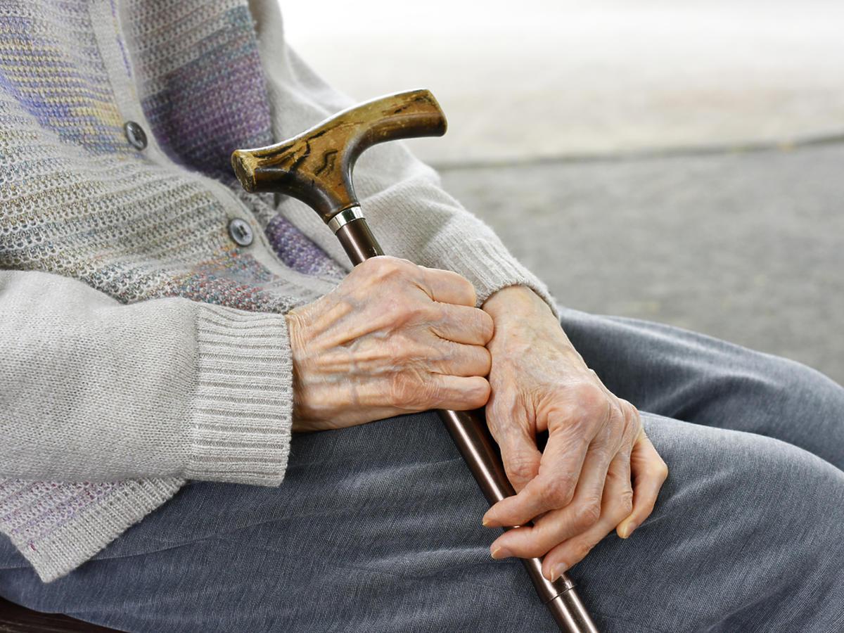 Starsza kobieta odpoczywa siedząc na krześle.