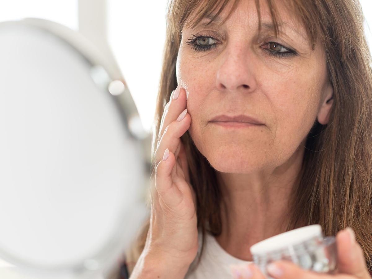 starsza kobieta smaruje twarz przed lustrem