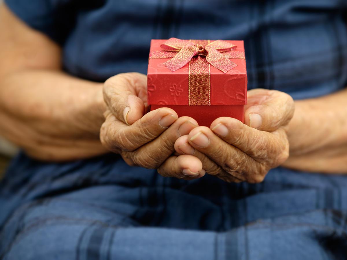 starsza kobieta trzymająca w dłoniach prezent
