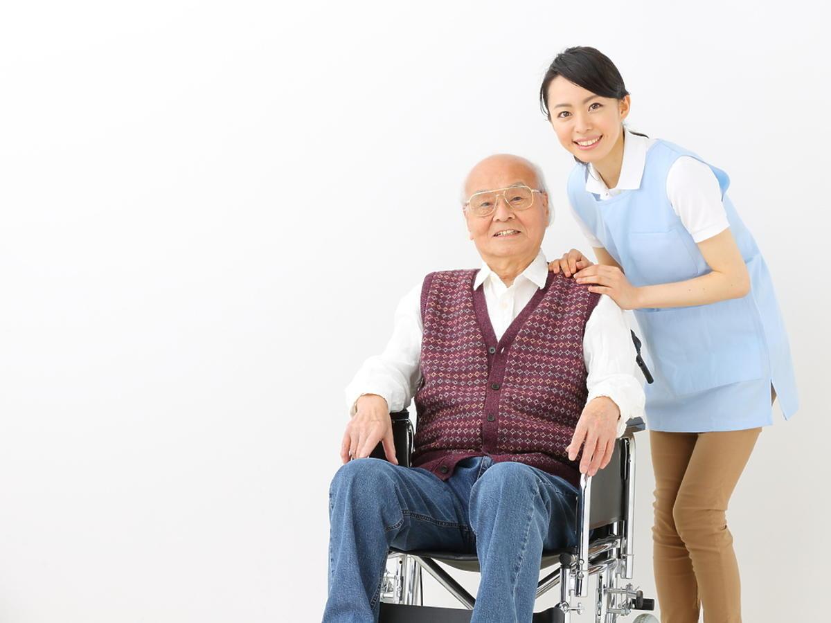 Starszy Chińczyk siedzi na wózku, a za nim stoi młoda kobieta
