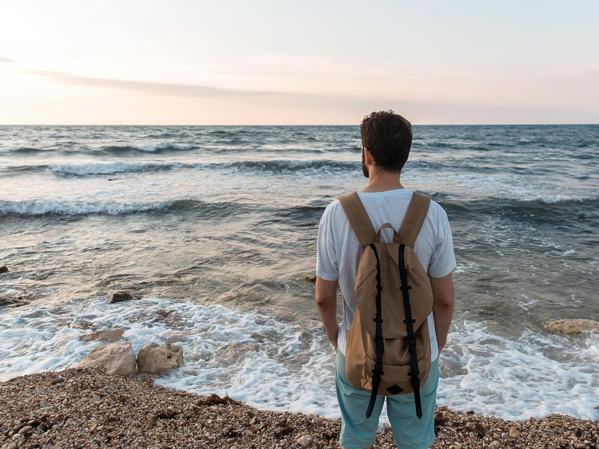 Stojacy tyłem chłopak z plecakiem nad morzem