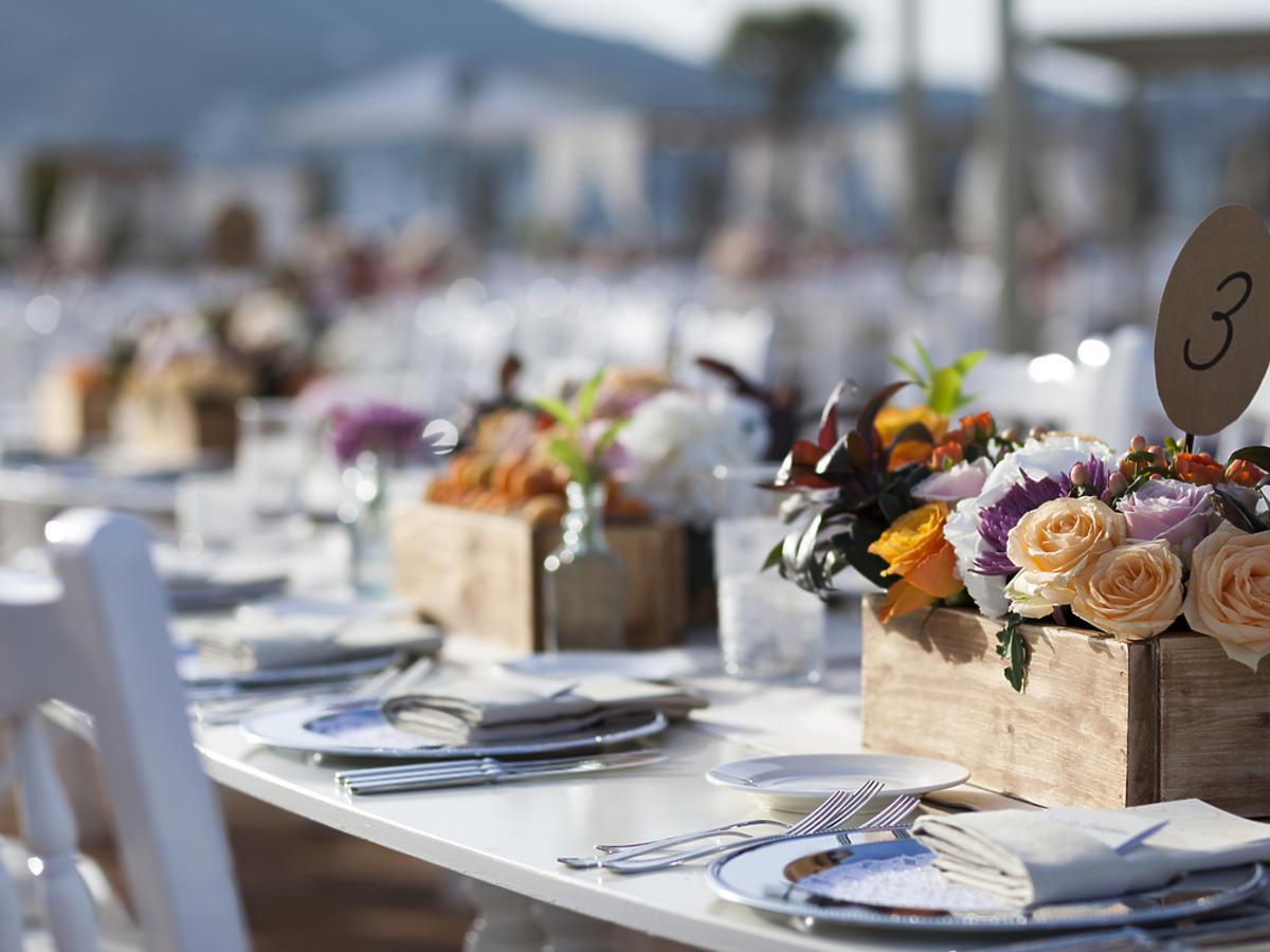 Stół weselny. Kwiaty w drewnianych skrzyneczkach. Elegancja zastawa.