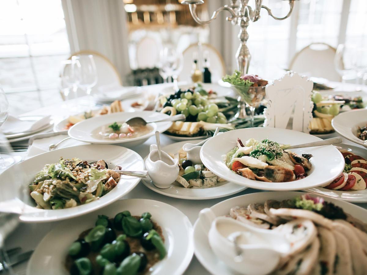 Stół weselny zastawiony kilkunastoma talerzami z nowoczesnym, apetycznym jedzeniem.