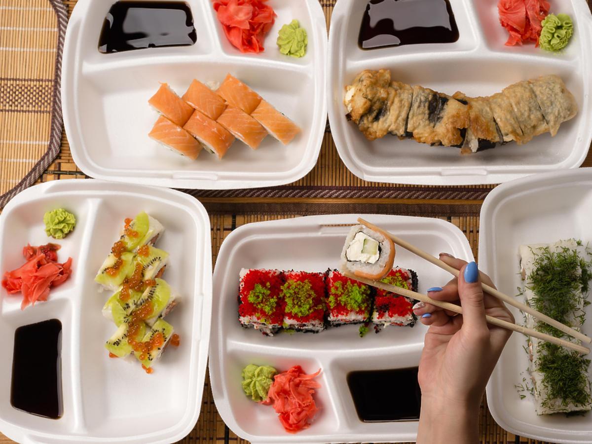 Stół zastawiony sushi i innymi przekąskami. Widoczne też pałeczki, którymi ktoś nabiera jedzenie.