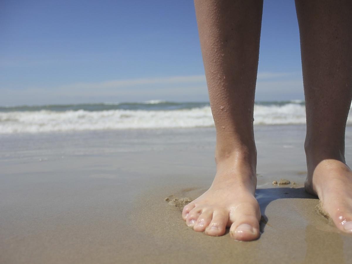 stopy na piasku nad morzem
