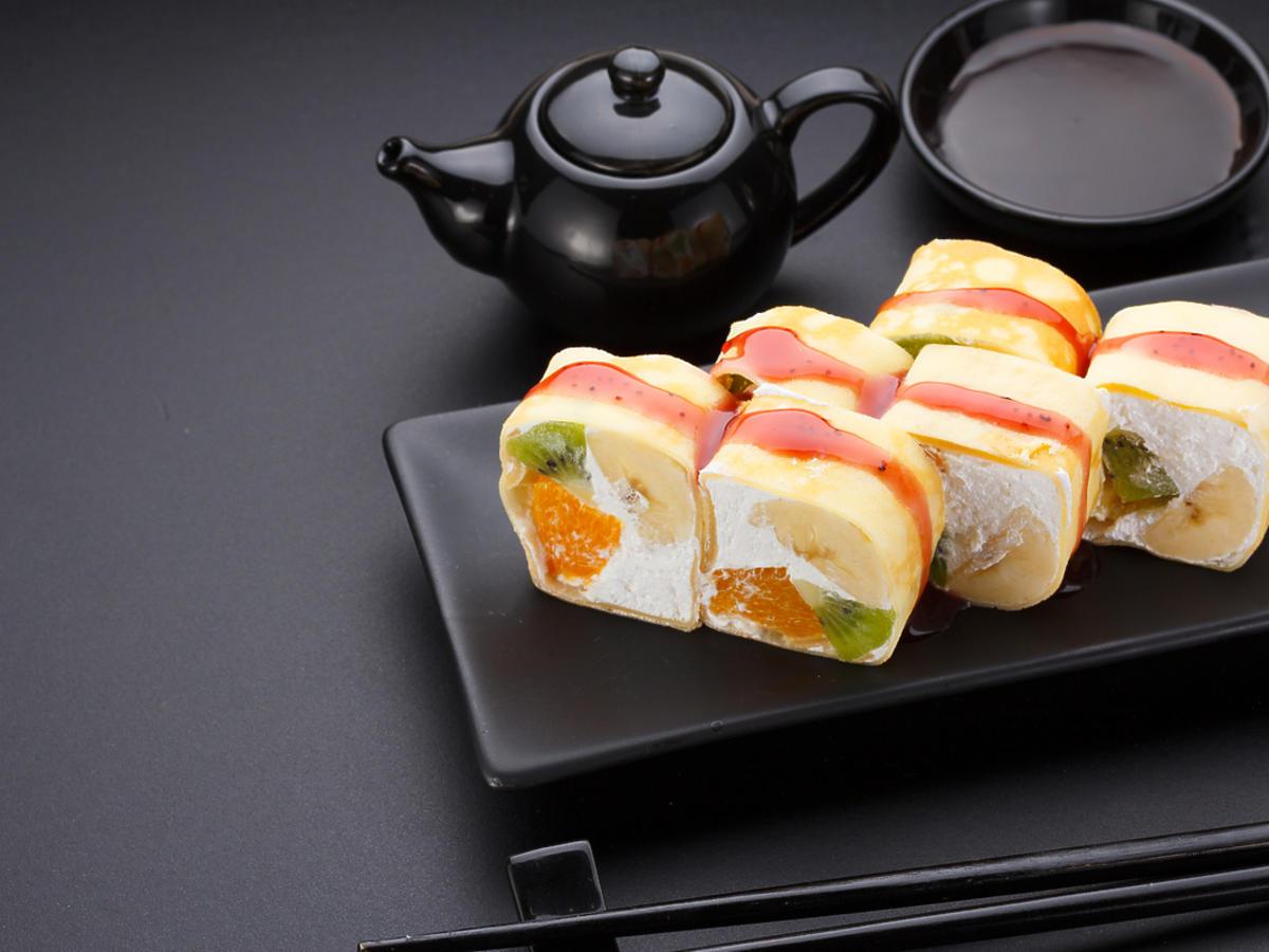 Sushi z owoców podane na eleganckich podłóżnych talerzykach.