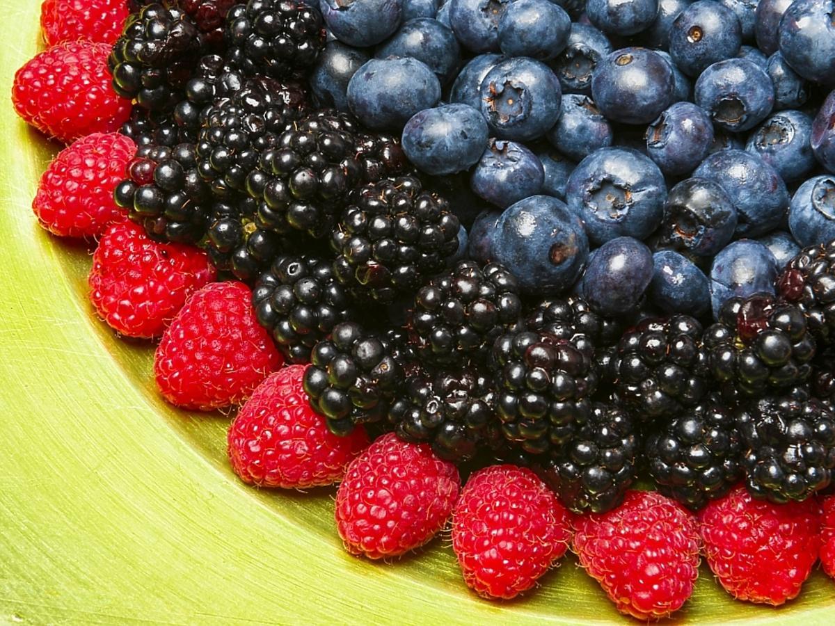 świeże owoce na talerzu: maliny, jeżyny, borówki