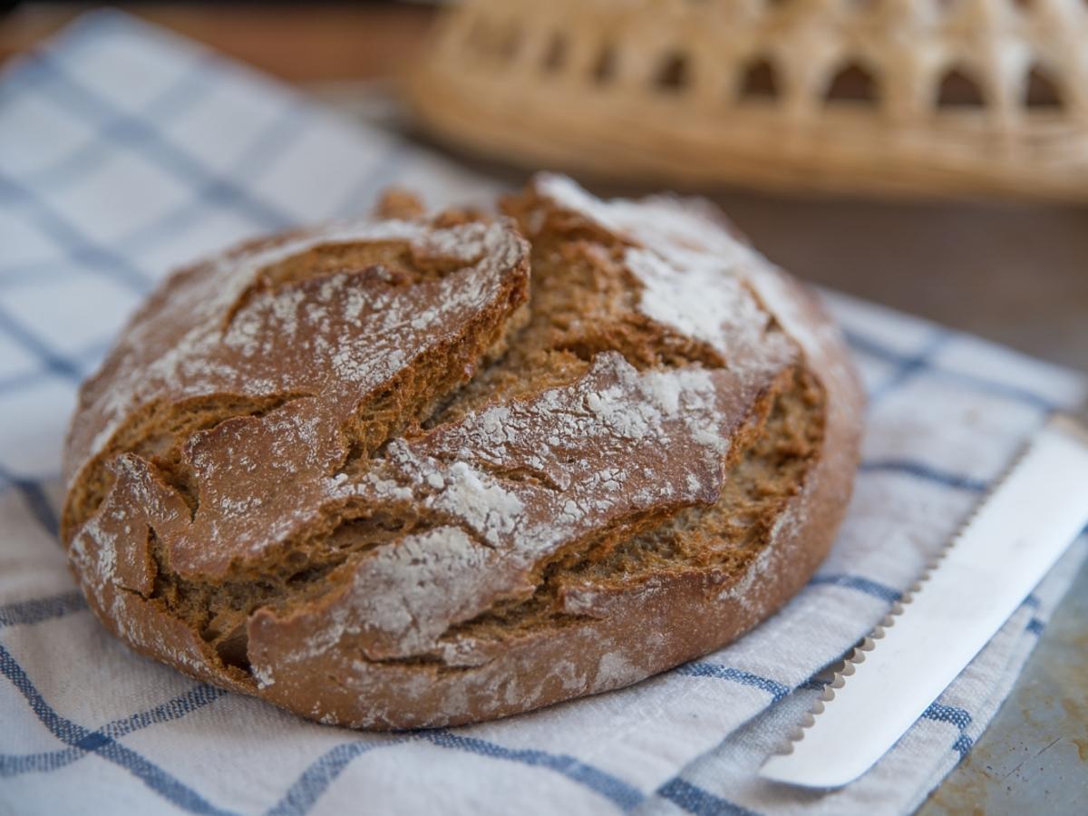 świeżo upieczony chleb razowy leży na lnianej ściereczce