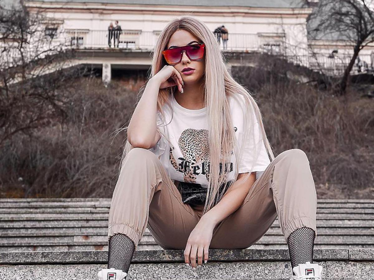 Sylwia Przybysz na schodach w beżowych spodniach