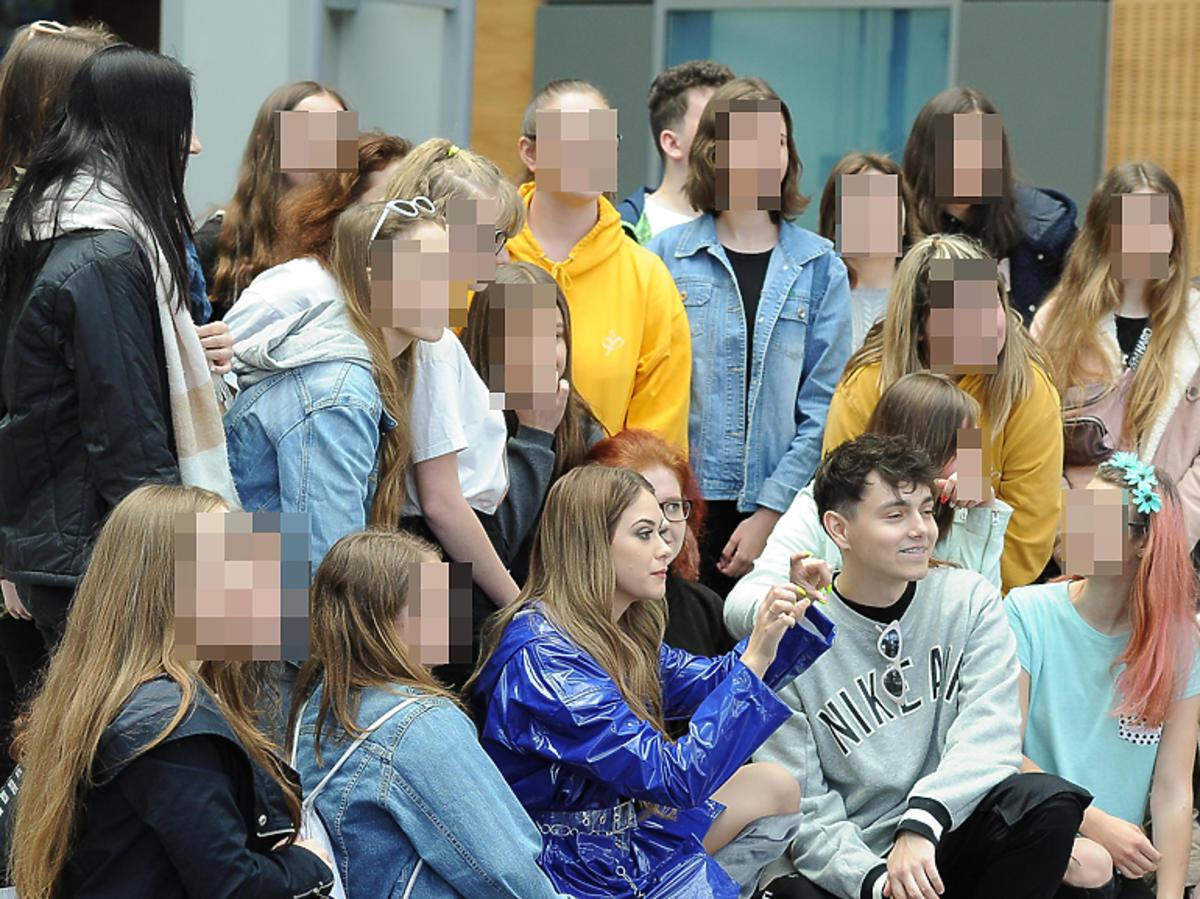 Sylwia Przybysz w fioletowej sukience i Jan Dąbrowski w szarej bluzie z fanami