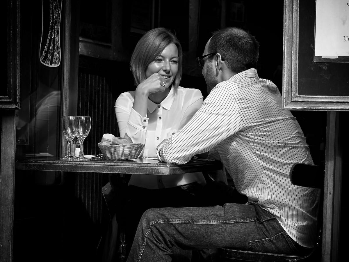 Szczęśliwa para siedząca przy stoliku w kawiarni.