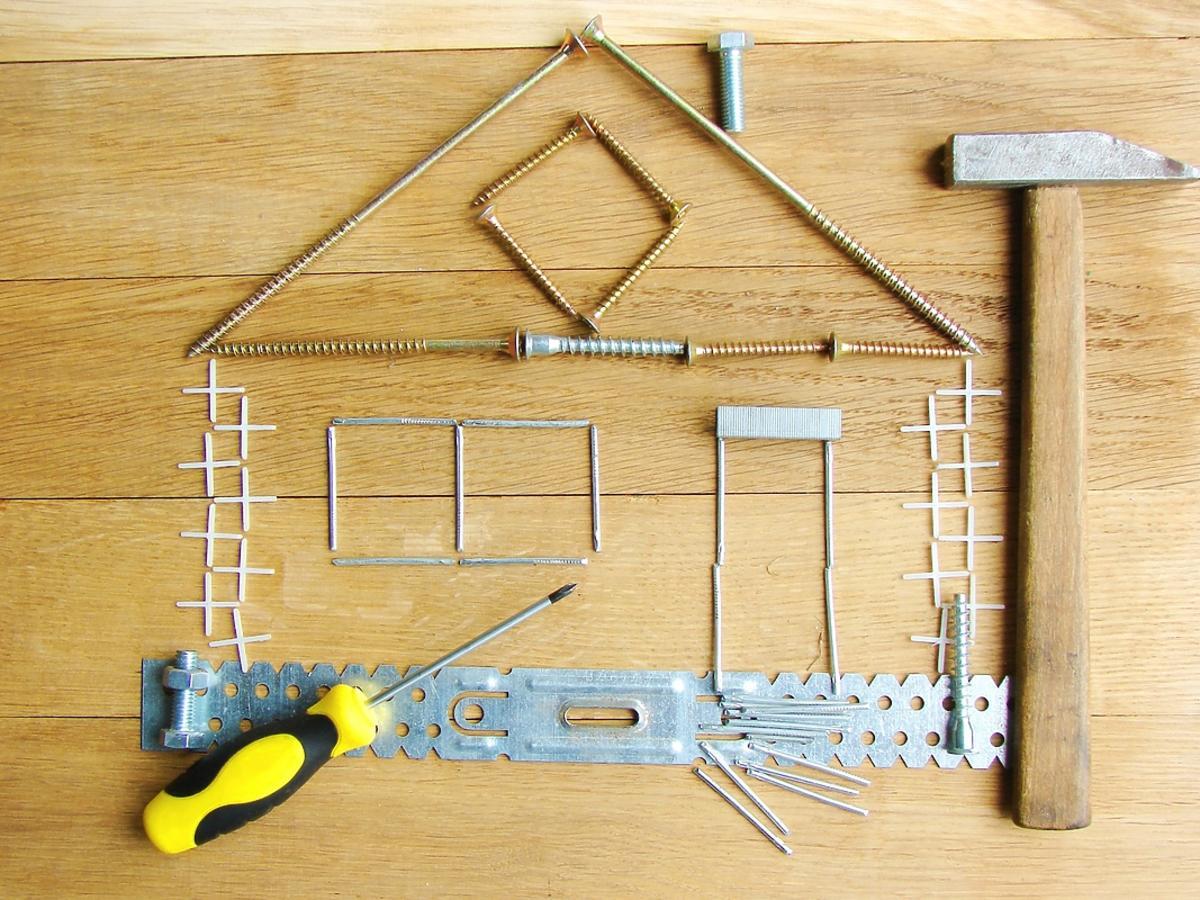 Szkielet domu ułożony ze śrubek i narzędzi na drewnianym tle.