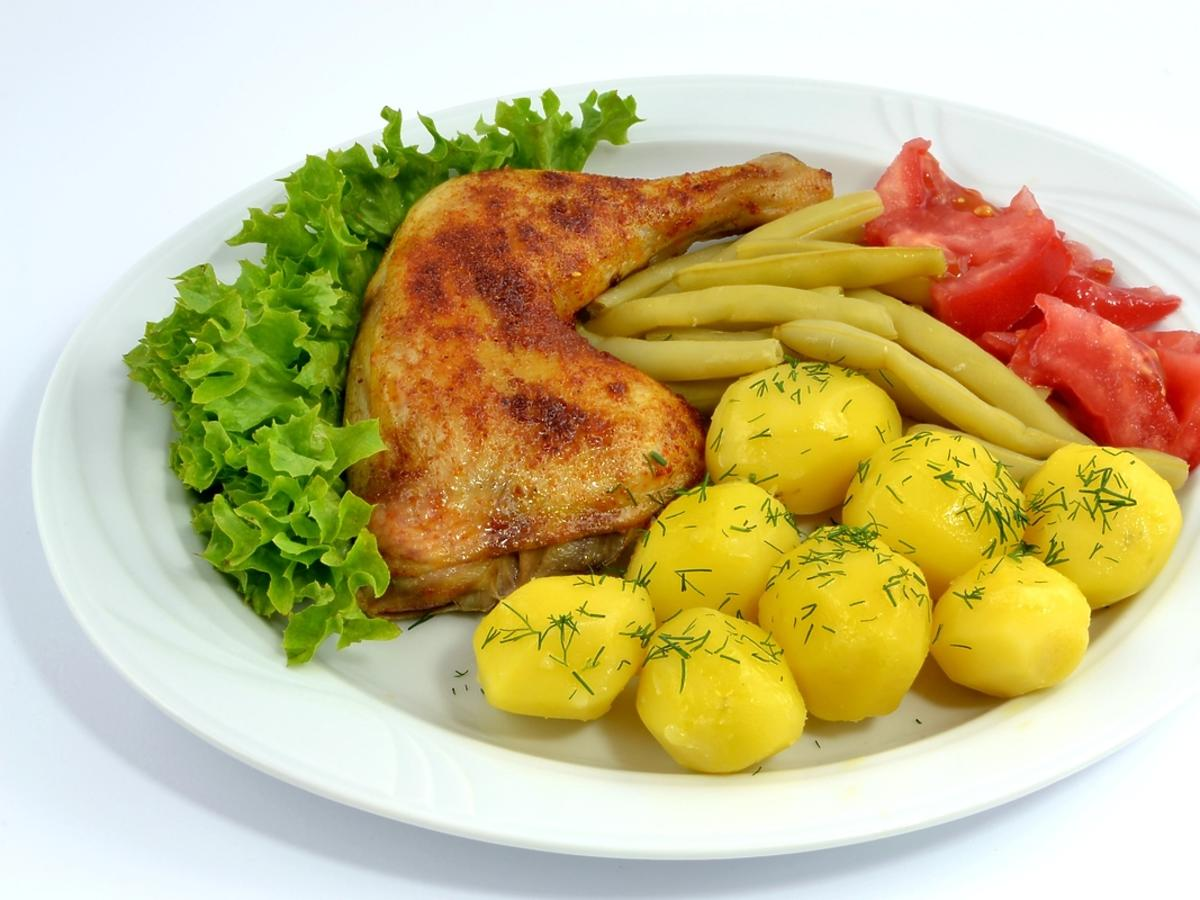 Talerz z drobiowym udkiem, ziemniakami, fasolką szparagową i pomidorami, przybrany sałatą