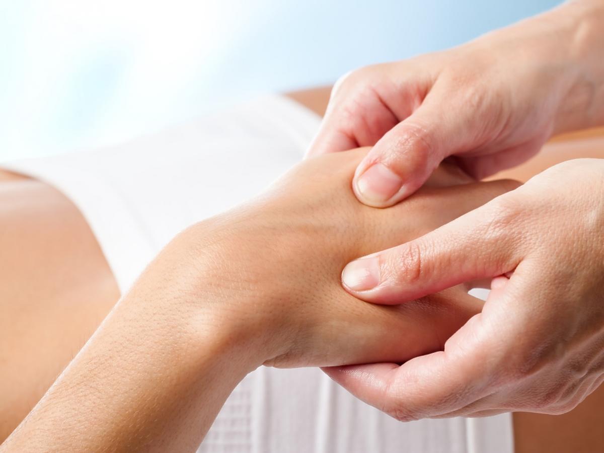 terapeuta dotyka kobiecej dłoni