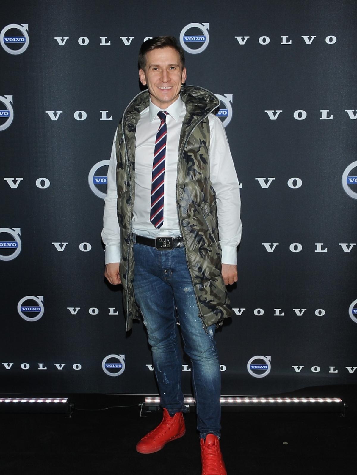 Tomasz Barański w białej koszuli, krawacie, kamizelce i dżinsach