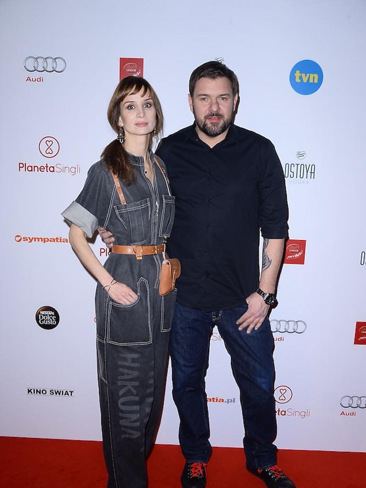 Tomasz Karolak w czarnej koszuli i Viola Kołakowska w czarnym dżinsowym kombinezonie