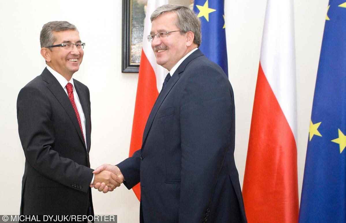 Tomasz Tomczykiewicz w garnuturze i Bronisław Komorowski w garniturze ściskają sobie dłonie